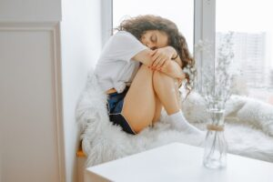 A young woman not feeling well, wondering if her symptoms are related to her period or possible pregnancy.